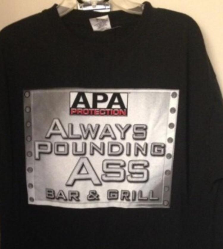"""A vintage WWE shirt for the APA that reads """"Always Pounding Ass Bar & Grill"""""""