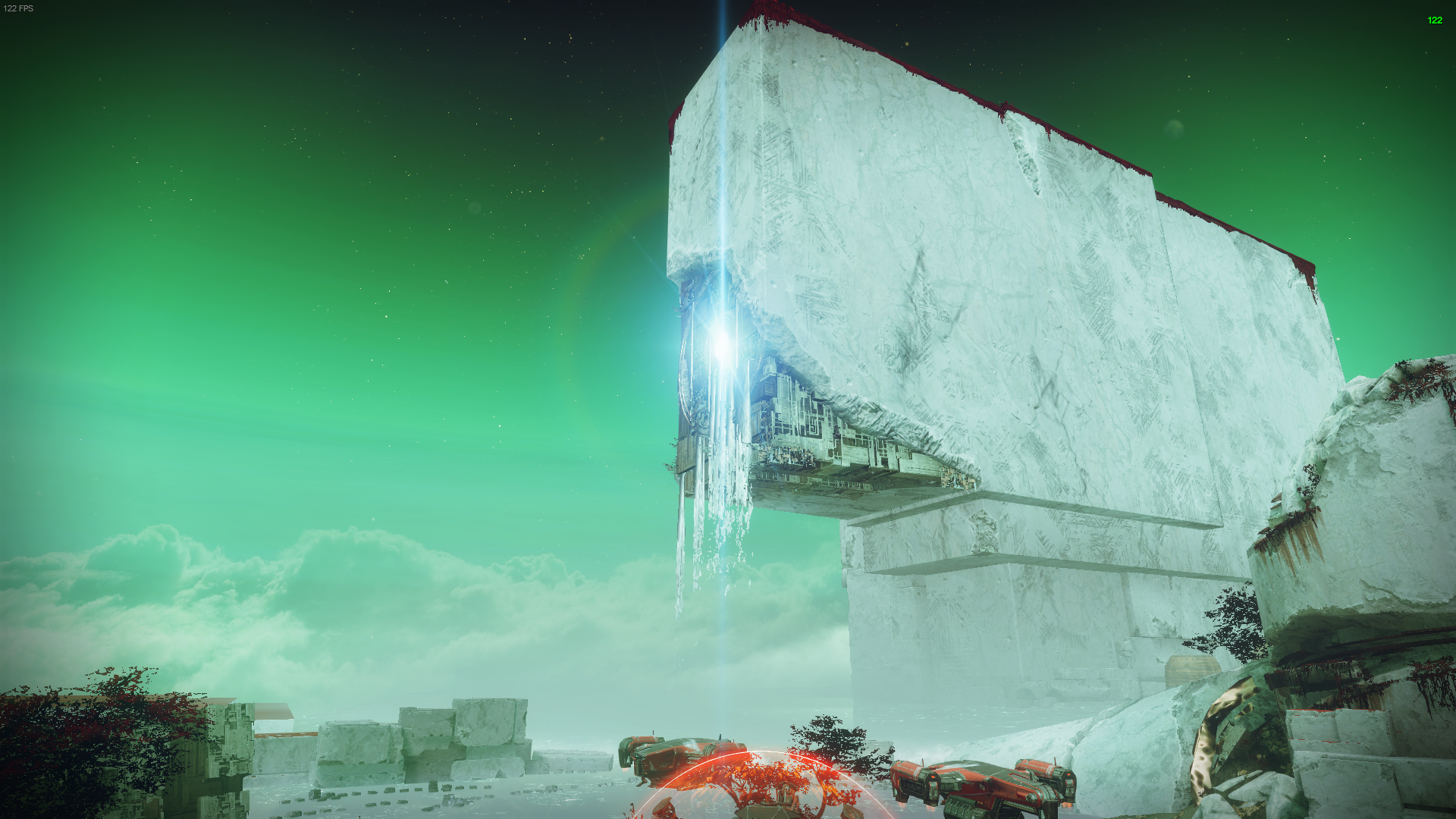 A square Vex monolith with and overhang which has exposed machinery rather than white rock. A light shines from within and fluid falls out. Red moss circles the top.