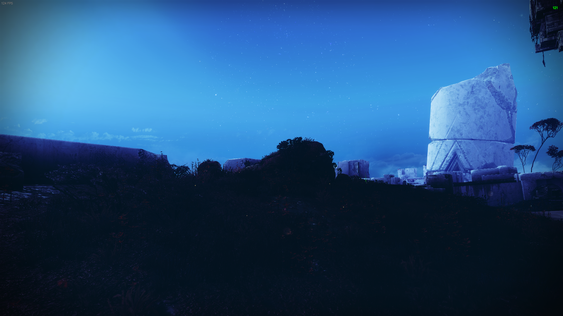 First person view of a Guardian walking up a hill on Nessus at night. The ground is almost entirely black while the sky shines a bright blue. A white Vex tower is in the background.