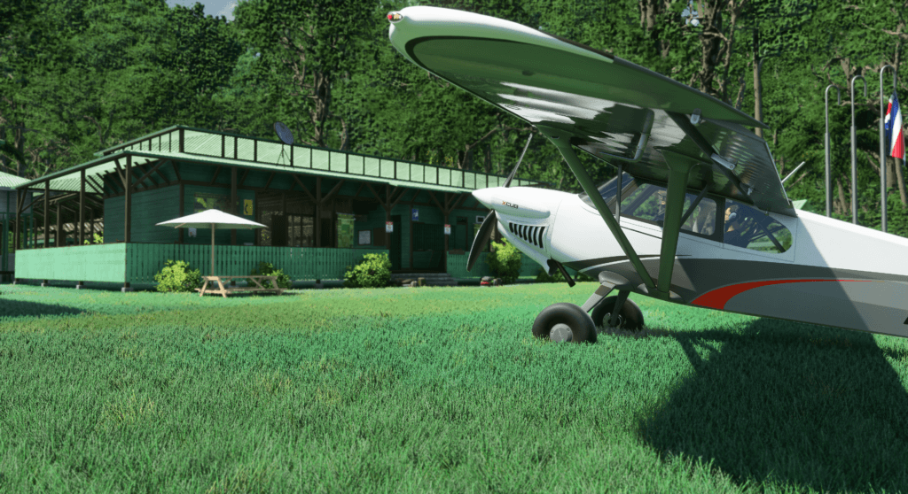 An XCub sits on the grass nearby a building in a forested area